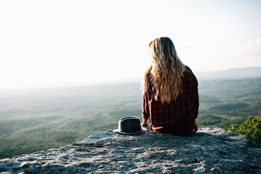 woman sitting in nature meditating